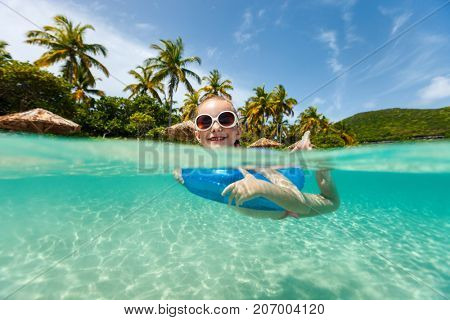 Split underwater and above photo of a little girl swimming in a tropical ocean with inflatable ring