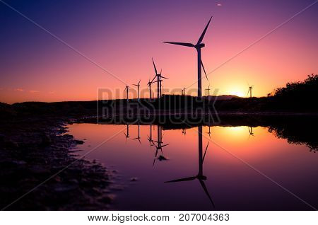 Wind turbines at a wind farm with the silhouettes reflected on the water surface at sunset, Crete, Greece