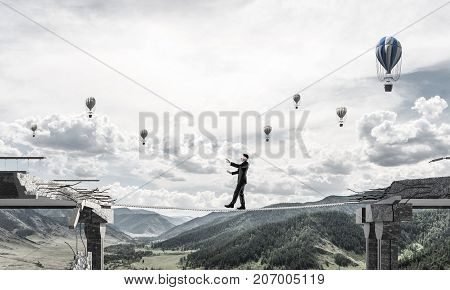 Businessman walking blindfolded on rope above huge gap in bridge as symbol of hidden threats and risks. Flying balloons and nature view on background. 3D rendering.