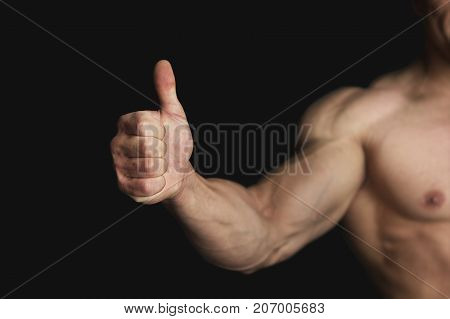 Strong Athletic Man Showing Big Thumb on Black Background