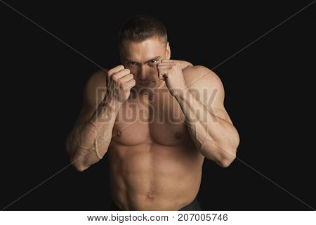 Strong Young Man Boxer Looking at Camera on Black Background
