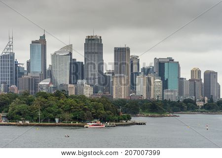 Sydney Australia - March 21 2017: Green trees of Botanical garden in front of city skyline section under gray sky. Shot from the bay: people on shore line boats and buoys.
