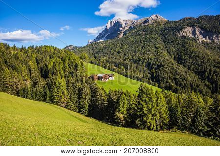 Dolomites, Val de Funes valley. Lovely day. Picturesque mountains surround the green alpine meadows of the valley