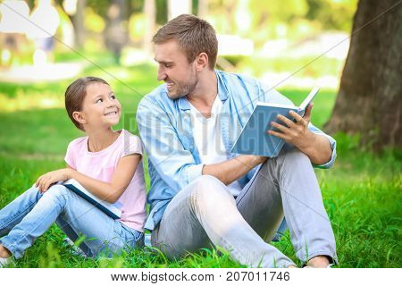 Young man and his little daughter reading books in park