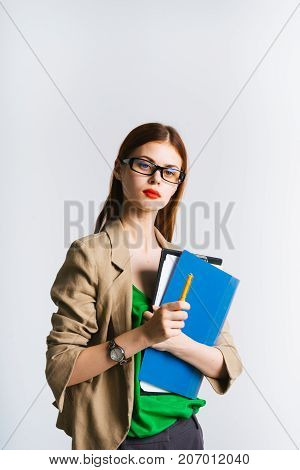 bright girl with glasses and with red lipstick holds folders in her hands and looks closely