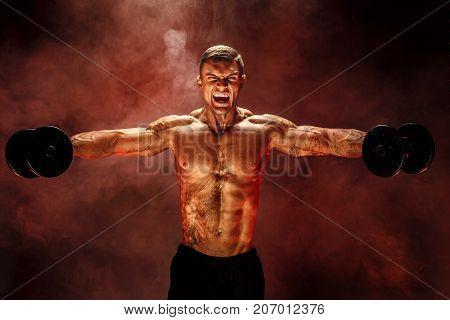 very brawny guy bodybuilder, execute exercise with dumbbells, on deltoid muscle shoulder. Sream for motivation. Shot on studio red smoke background.
