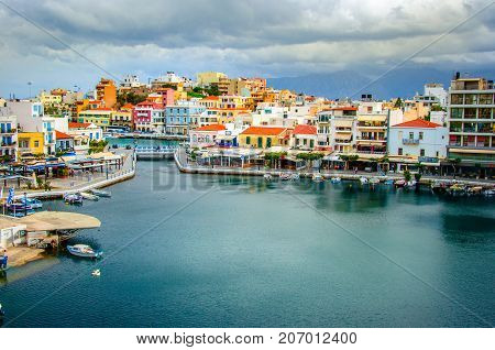 The lake Voulismeni in Agios Nikolaos,  a picturesque coastal town with colorful buildings around the port in the eastern part of the island Crete, Greece The lake Voulismeni in Agios Nikolaos,  a picturesque coastal town with colorful buildings around th