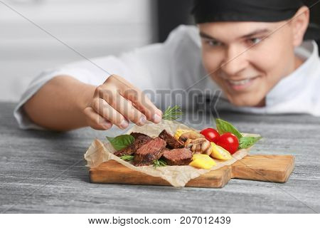 Chef decorating tasty juicy meat on table
