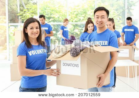 Two happy teen volunteers holding box with donations indoors