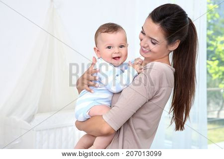 Mother holding cute baby after bathing at home