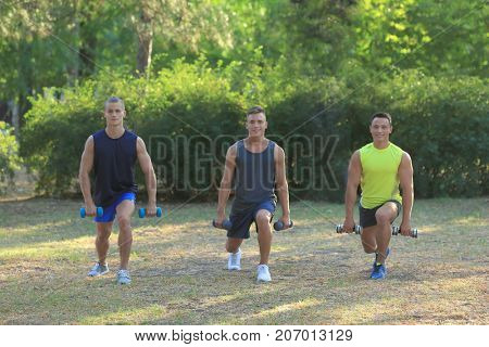 Young sporty men with dumb-bells doing exercise outdoor