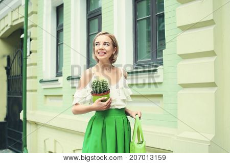 Young happy hipster woman in green skirt holding cactus outdoors