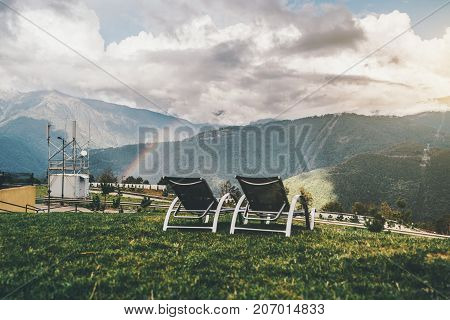 Two empty daybeds on grass glade and stunning rainbow mountains landscape behind; void recliners on autumn meadow with dramatic iris leaping over the hills in the background sunny day with rain