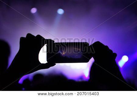 Woman capturing on video open air rock concert