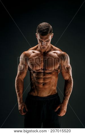 Very brawny guy bodybuilder posing. Beautiful sporty guy male power. Fitness muscled man in studio. Dark background.