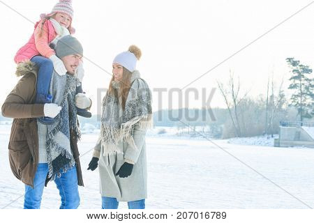 Family with child on winter holidays walking in the nature