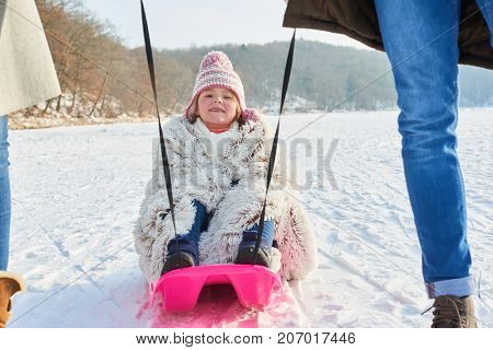 Child sledding or toboggan on snow with her happy family