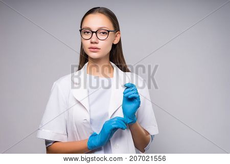 Careful attentive intern doctor in medical gown and gloves