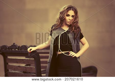 Young woman with long curly hairs walking in city street. Stylish fashion model in long vest outdoor
