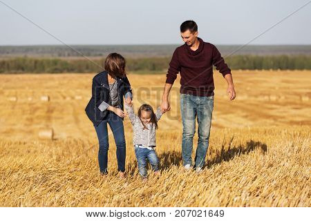 Happy young family with 2 year old girl walking in a harvested field. Father mother and daughter outdoor