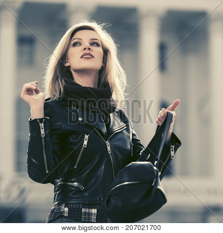 Young fashion blond woman with handbag walking in city street. Stylish female model in black biker jacket outdoor