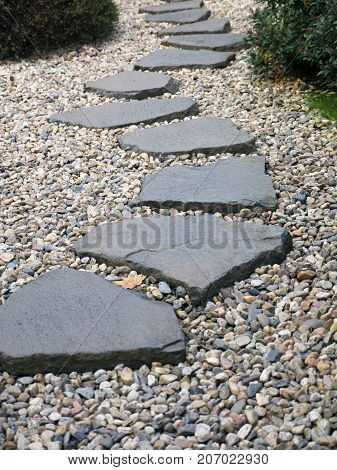 Path of plated stones on gravel bed in Japanese Garden. Meditative stone walkway. Garden architecture, pathway accessory to garden pond.