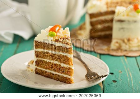 A piece of carrot cake with cream cheese frosting and little carrots on top