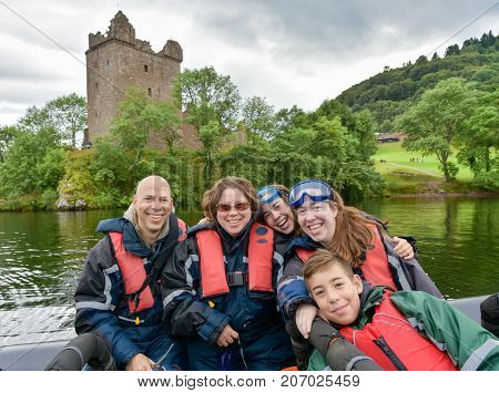 Tourists speedboating on a RIB boat with near Urquhart Castle on the iconic Loch Less Scotland