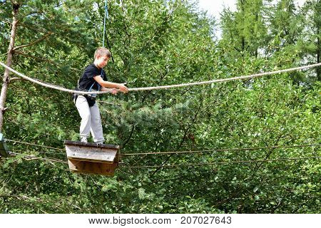 Young Teenage Woman In A Treetop Rope Park Adventure