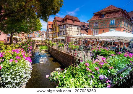 Beautiful view of the historic town of Colmar, also known as Little Venice, people at cafe, traditional colorful houses on idyllic river Lauch in summer, Colmar, Alsace, France on July 21, 2017.