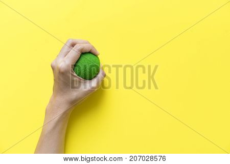 woman hand holding a stress ball on yellow background