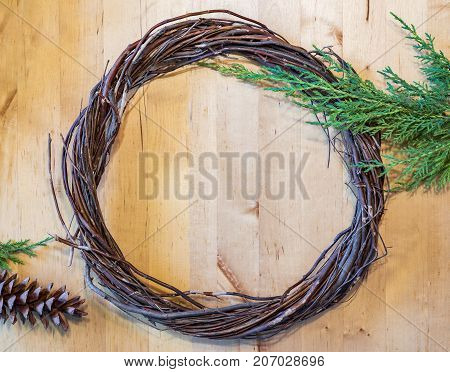 Rustic wreath made a twigs and branches on simple wooden background with pine cone and evergreen branches. Christmas image with space for text