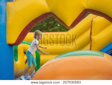 Little girl fun fun on an inflatable trampoline. The concept of a happy childhood.