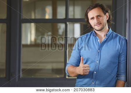 Portrait of a cheerful young man showing okay gesture on the old window background
