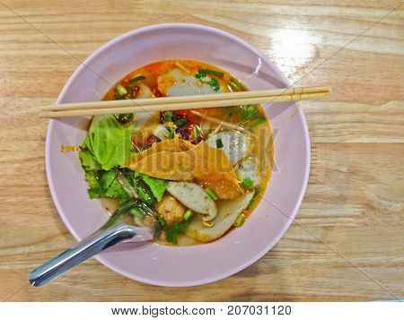 noodle tom yum with pork / spicy thai noodle on wood table