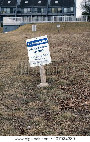 BAY VIEW, MICHIGAN / UNITED STATES - MARCH 30, 2017: A sign, posted beside the Little Traverse Wheelway, indicates that the walkway and deck are private, and for Tannery Creek residents and guests only.