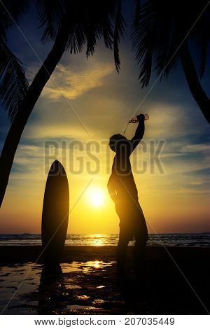 Silhouette of surf man stand with a surfboard and coconut palm drink water from bottle. Surfing at sunset beach. Outdoor water sport adventure lifestyle.Summer activity. Asia male model in his 20s