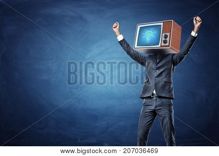 A victorious businessman with arms raised up and a retro TV showing a glowing bulb on his head. Business and success. Profitable idea. Game-changing invention.