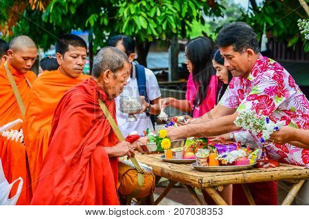 Kanchanaburi Thailand - April 12 2014: Buddhist people offering alms to monks in the morning in Sangkhlaburi of Kanchanaburi Thailand