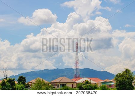 Telecommunications tower in the village with mountainous background and clouds in the sky.