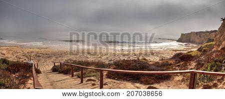 Fog drifts in over the ocean at Crystal Cove state beach on the edge of Laguna Beach and Corona del Mar California in fall.