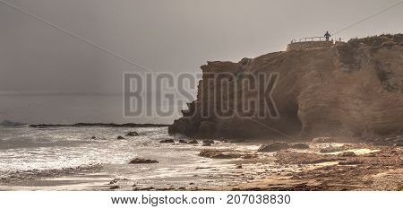 Lone man stands at a vista as Fog drifts in over the ocean at Crystal Cove state beach on the edge of Laguna Beach and Corona del Mar California in fall.