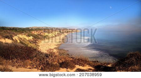 Moon in the sky as Fog drifts in over the ocean at Crystal Cove state beach on the edge of Laguna Beach and Corona del Mar California in fall.