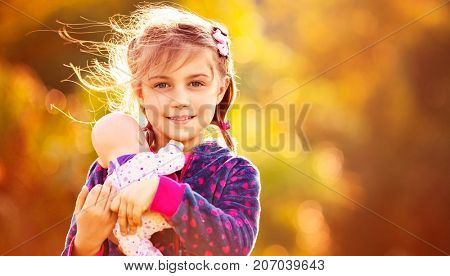 Portrait of a sweet baby girl with doll over orange autumnal foliage background, happy child playing mother's daughters outdoors in fall sunny day