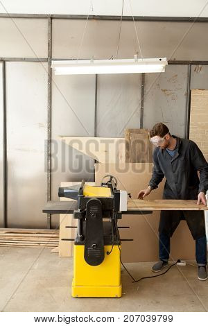 Worker in safety glasses putting untreated wooden board in thickness planer machine. Carpenter producing lumber with powerful machine tool in sawmill. Skilled joiner working in woodworking workshop