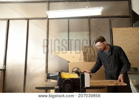 Carpenter trims massive wooden board on woodworking thickness planer machine. Joiner working at own small sawn timber manufacture. Young entrepreneur developing his local sawmill, furniture business