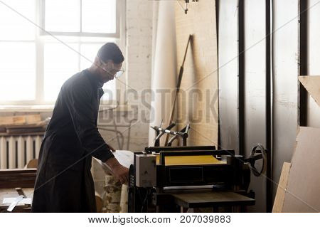 Tradesman putting wooden board in machine tool in carpentry. Small business owner working at stationery thickness planer machine in workshop. Professional joiner using industrial equipment in sawmill