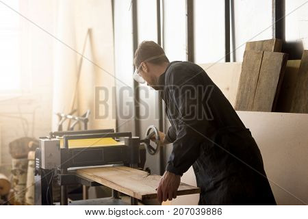 Back view of young carpenter or craftsman wearing working clothes and protective eyewear woodworking in small workshop interior, operating stationary power planer, processing trimming wooden plank