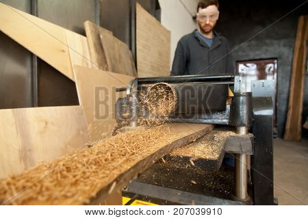 Stationary power planer processing wooden flooring board, making sawdust, male carpenter operator in the background controlling process. Joiner operating plant equipment, woodworking machine