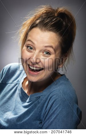 Thrilled woman smiling in surprise. Amazed face expression.